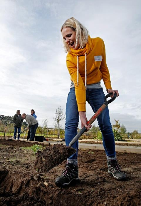 A woman wearing a yellow hoodie and blue jeans uses a garden spade to move soil.