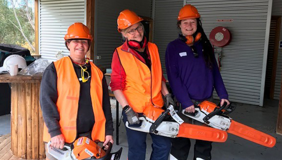 Three women with chainsaws