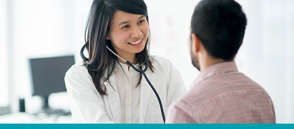 Femme médecin tenant stéthoscope au patient