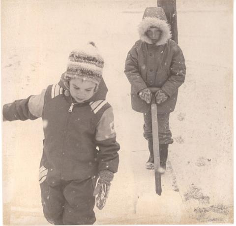 This is a photograph from 1975. It shows two children from Churchill Cres. They are dressed in winter clothes and one is shoveling snow along the sidewalk while the other walks infront of the shovel.