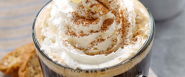 Close up of a coffee with whipped cream on top.