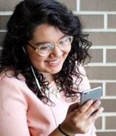 A woman in a pink sweater and glasses standing against a brick wall smiles into her smartphone.