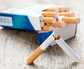 Cigarette snapped in two in front of package of cigarettes