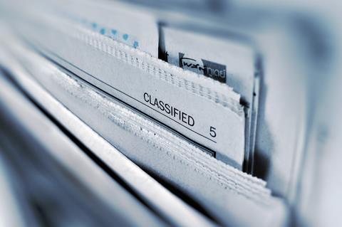 """Closeup of the tops of newspapers with the section """"Classified"""" visible"""