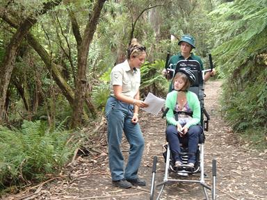 A man and a woman helping a woman in a trailrider