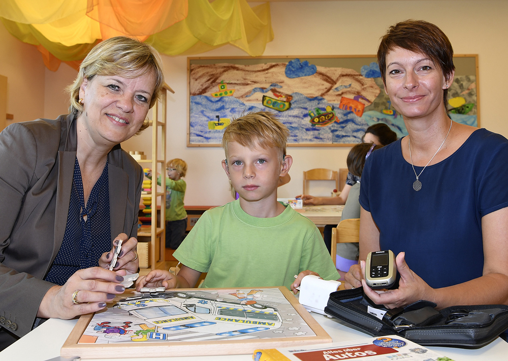 "Photo: Barbara Schwarz visiting Emil Hausmann and his mother Petra Hausmann (association ""Eltern und Freunde Hörgeschädigter"") at the kindergarten Obergrafendorf , where she was informed about the use of FM systems.  (© NÖ Landespressedienst/Filzwieser)"