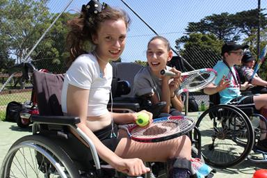 Two girls holding tennis rackets