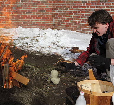 Image of student firing pottery