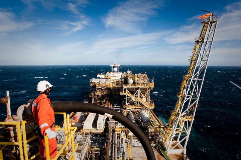Technician in orange high-vis gear standing on an oil ship in the middle of the ocean.