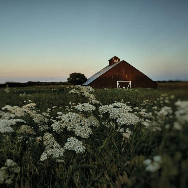 A full moon rises above a barn in a field.