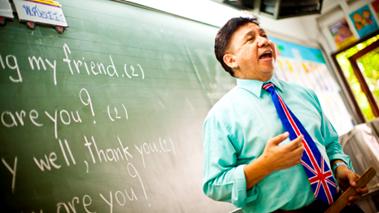 A teacher stands in front of a blackboard