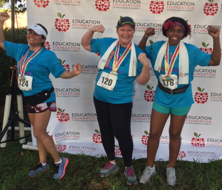 three Clerk employees in front of Heroes for Education 5K banner showing off medals