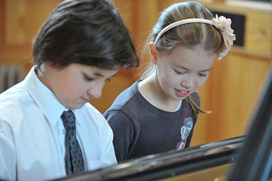 Young boy and girl playing the piano