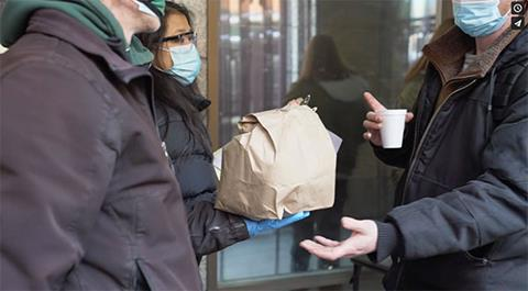 A person in a face mask holds out a bag lunch to another person.