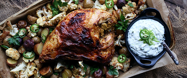 Photo of sheet pan full of roasted vegetables, roasted turkey, topped with jalapenos and cilantro with a side of raita.