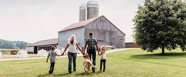 Photo of a family walking toward one of their barns on their dairy farm.