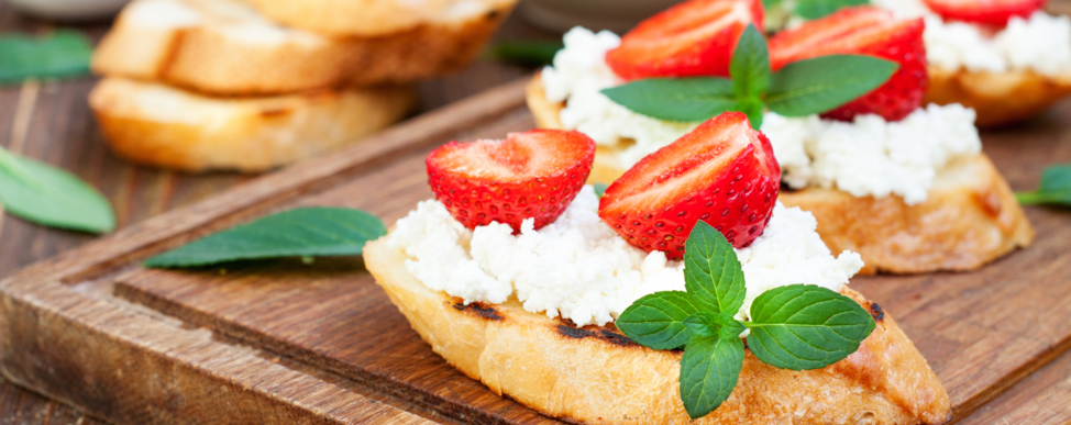 Photo of grilled baguette topped with a mixture of blue cheese and cottage cheese, along with strawberries and basil.