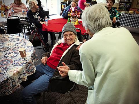Imagen de residentes mayores de Burbank Housing disfrutando de una conversación