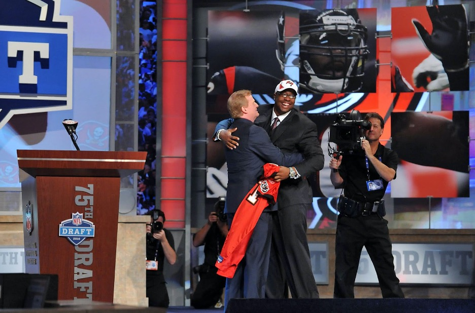 NFL Commissioner hugging draftee on stage during 75th draft